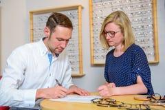 In der jungen Frau und im Mann des Optikergeschäftes, die neue Gläser vorwählt und Stockbilder