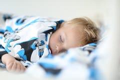Der Jungenjunge schläft auf einer netten Bettwäsche lizenzfreies stockbild