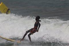 Der Jungensurfer in populärem Strand Lagos, Tarkwa-Bucht, Lagos Nigeria stockbilder