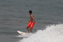 Der Jungensurfer in populärem Strand Lagos, Tarkwa-Bucht, Lagos Nigeria stockfotos