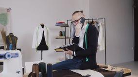 Der junger Modedesigner oder Schneider, die auf Tabelle im Atelier und in Unterhaltungstelefon sitzen und macht Anmerkungen in se stock video footage