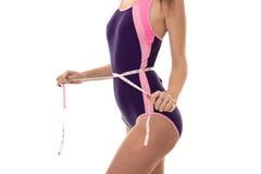 Der Körper eines attraktiven jungen Mädchens in einem Körper, der heraus ein messendes Band der Taille misst, wird auf einem Weiß Stockfotografie