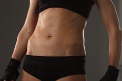 Der Körper eines jungen athletischen Mädchens auf dunklem Hintergrund Stockfoto
