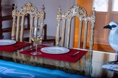 Der Küchentisch ein Glas des Stuhls des Weins und zwei Weinlese gegen das Fenster Stockfotos