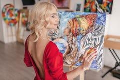 Der Künstler in einem roten Kleid Stockfoto