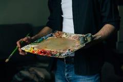 Der Künstler hält eine Palette mit Farben und einer Bürste Ein Mann in den Jeans und in einem schwarzen Hemd Lizenzfreie Stockbilder