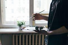 Der Künstler hält eine Palette mit Farben und einer Bürste und wird auf Segeltuch malen über vom Fenster Stockbild