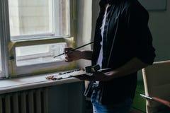 Der Künstler hält eine Palette mit Farben und einer Bürste und wird auf Segeltuch malen über vom Fenster Stockbilder