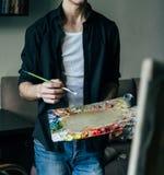 Der Künstler hält eine Palette mit Farben und einer Bürste und wird auf Segeltuch malen Stockfotos