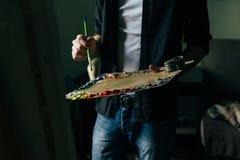 Der Künstler hält eine Palette mit Farben und einer Bürste und wird auf Segeltuch malen Lizenzfreie Stockfotografie