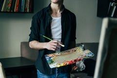 Der Künstler hält eine Palette mit Farben und einer Bürste und wird auf Segeltuch malen Lizenzfreies Stockbild