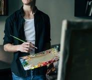 Der Künstler hält eine Palette mit Farben und einer Bürste und wird auf Segeltuch malen Lizenzfreie Stockbilder