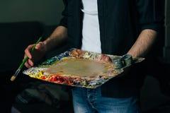 Der Künstler hält eine Palette mit Farben und einer Bürste und wird auf Segeltuch malen Stockfotografie