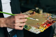 Der Künstler hält eine Palette mit Farben und einer Bürste und wird auf Segeltuch malen zu Ölfarben mischen Lizenzfreie Stockfotografie