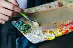 Der Künstler hält eine Palette mit Farben und einer Bürste und wird auf Segeltuch malen zu Ölfarben mischen Stockfoto