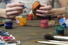 Der Künstler malt das Haus und die Farbe und die Bürste Lizenzfreie Stockfotos