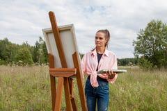 Der Künstler malt ein Bild auf dem Gebiet stockbilder
