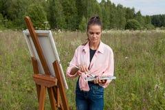 Der Künstler malt ein Bild auf dem Gebiet stockfoto