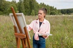 Der Künstler malt ein Bild auf dem Gebiet lizenzfreies stockbild