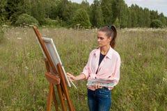 Der Künstler malt ein Bild auf dem Gebiet lizenzfreie stockfotos