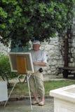 Der Künstler steht vor einem Segeltuch und einer Farbe Stockbild