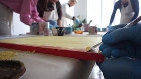 Der Künstler verkratzt die Farbe mit einer Spachtel Malen Sie Dosen Gelber Lack stock footage