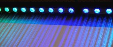Der künstliche Regen, der von der Decke kommt, wird durch runde Glühlampen mit farbigem Licht belichtet Stockbild