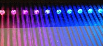 Der künstliche Regen, der von der Decke kommt, wird durch runde Glühlampen mit farbigem Licht belichtet Stockfotos