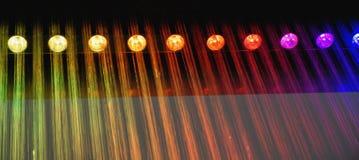 Der künstliche Regen, der von der Decke kommt, wird durch runde Glühlampen mit farbigem Licht belichtet Lizenzfreies Stockfoto