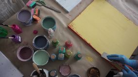 Der K?nstler verkratzt die Farbe mit einer Spachtel Der Lehrer fordert auf Malen Sie Dosen Gelber Lack stock footage