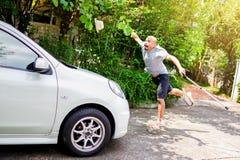 Der kahle asiatische Mann wurde durch ein weißes Auto vor seinem Haus geschlagen stockfotos