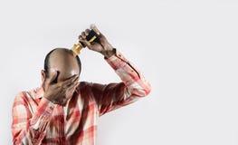 Der kahle Mann, der sein Gesicht bedeckt und Haar anwendet, wachsen Öl im weißen Hintergrund mit Raum für Text stockbild