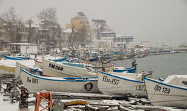 Der Kai des Fischers in schneebedecktem Pomorie in Bulgarien Lizenzfreies Stockfoto
