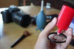 Der Kameraobjektivreiniger und eine Hand, welche die Kamera säubern Stockfotos