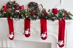 Der Kamin verziert mit roten Weihnachtswollsocken Stockfoto