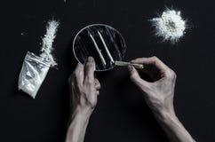 Der Kampf gegen Drogen und Drogensuchtthema: Handsüchtiglügen auf einer dunklen Tabelle und um sie sind Drogen, ein Spitzenstudio Lizenzfreie Stockbilder