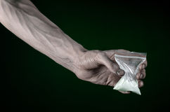 Der Kampf gegen Drogen und Drogensuchtthema: schmutzige Hand, die ein Taschensüchtigkokain auf einem dunkelgrünen Hintergrund im  Stockfotografie