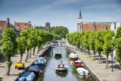 Der Kanal, der die historische Mitte von Sloten kreuzt, zeichnete mit grünen Bäumen Lizenzfreie Stockfotografie