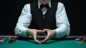 Der Kasinohändler, der das Schlurfen macht, betrügt mit den Karten und erhält As, glückliches Pokerspiel stock video