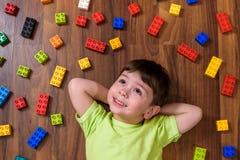 der kaukasische Junge, der mit vielen buntem Plastik spielt, blockiert Innen Aktive Kinderjungen, Geschwister, das Spaßerrichten  Lizenzfreies Stockbild