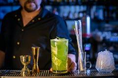 Der Kellner bereitet ein frisches, kaltes Cocktail auf dem Barzähler vor Gurkengetränk mit Alkohol und Kalk Unglaubliche Mischung Lizenzfreies Stockbild