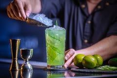 Der Kellner bereitet ein frisches, kaltes Cocktail auf dem Barzähler vor Gurkengetränk mit Alkohol und Kalk Unglaubliche Mischung Lizenzfreies Stockfoto
