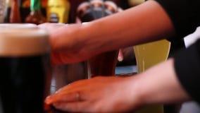 Der Kellner in der Bar holt und setzt an Tabelle verschiedene Grade von Bieren stock video footage