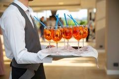 Der Kellner dient Cocktails auf einem Behälter Orange und rote Cocktails der Nahaufnahme mit Orange und Minze stockbild