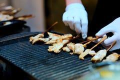 Der Kellner an einem Bankett brät Stücke des Huhns stockfotos