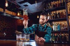 Der Kellner gießt Alkohol in ein Glas Stockfotografie