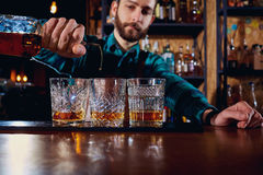 Der Kellner gießt Alkohol in ein Glas Nahaufnahme Stockbilder
