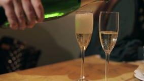 Der Kellner gießt Champagner in zwei Gläsern stock video