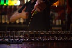 Der Kellner gießt viele alkoholischen Schüsse Lizenzfreies Stockfoto