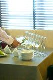 Der Kellner gießt Wein in Gläser Stockbild